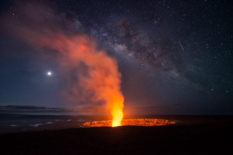 A volcano erupting under the night sky