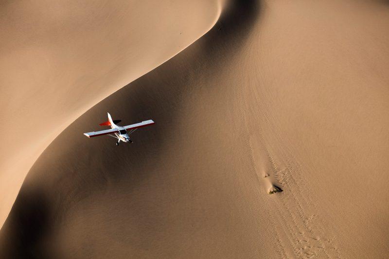 Plane flying over dunes